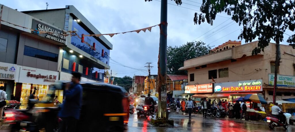 city centre of dharwad karnataka seen with traffic and auto rickshaw and lights of shop signboards