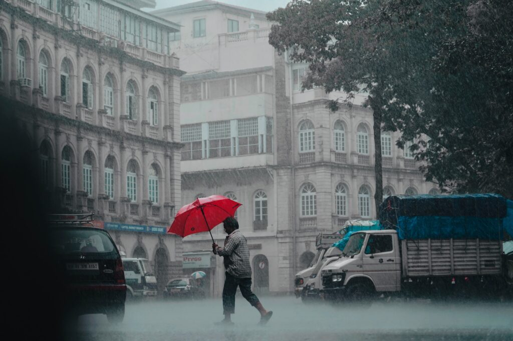 man with red umbrella crosses the street in mumbai during rains with the backdrop of buildings and traffic